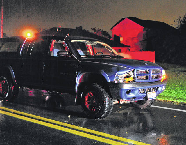 A pickup truck sits on Nashville Road after the driver struck a pedestrian around 7 a.m. on Wednesday morning.