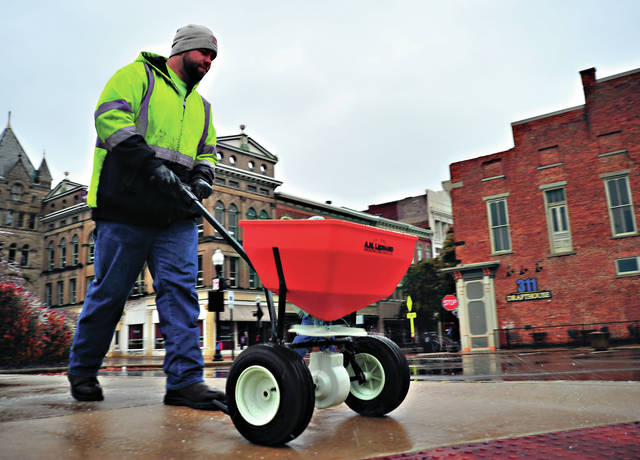 Mike Ullery | Daily Call City of Piqua Street Department employee Bill Cox spreads ice melter on sidewalks in the downtown area early Thursday morning after a night of freezing rain left ice covering exposed surfaces everywhere as the area got its first taste of winter weather for the season.