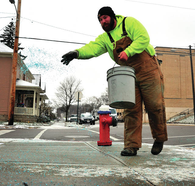 "Mike Ullery | Daily Call Kody Shade of Covington spreads ""ice-melter"" on a sidewalk in Piqua on Tuesday morning following a night of snow around the area. Shade works for Monroe Grounds Maintenance out of Troy."