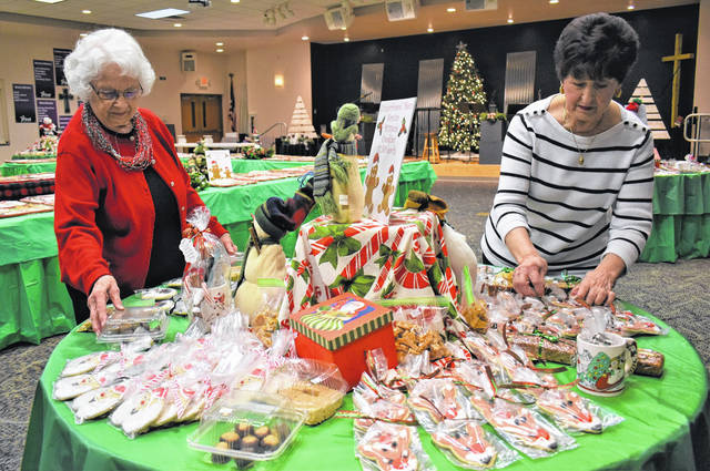 Cody Willoughby | Troy Daily News From left, Gerri Loar and President Kay Kaebnick of the Troy United Methodist Women prepare table displays ahead of the organization's annual Cookie Shoppe at First Place Christian Center, 16 W. Franklin St., Troy. The sale will be held on Saturday from 9 a.m. to noon, with hundreds of baked goods available to purchase for $7.50 per pound. All proceeds with benefit local missions and non-profit outreaches.
