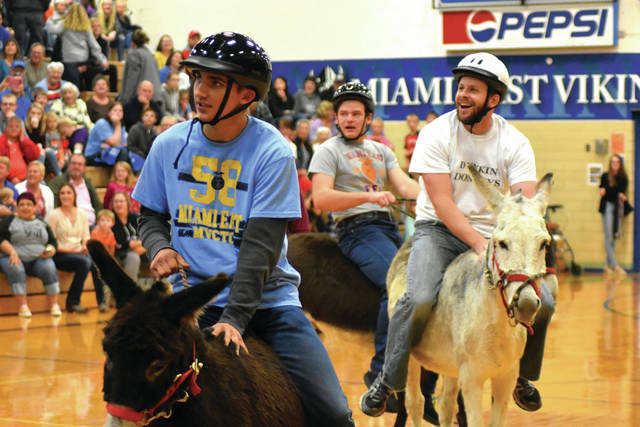 Cody Willoughby | AIM Media Midwest From left, Miami East FFA members Luke Gilliland and Ethan Bendickson, along with Kyle Magoteaux of Fletcher United Methodist Church, play in a game of donkey basketball on Sunday in the Miami East Board of Education gymnasium. The event vied members of Fletcher UMC, the Miami East FFA chapter, and teachers from Miami East Elementary, Junior High, and High School in a mini-tournament to raise money for the Fletcher food pantry.