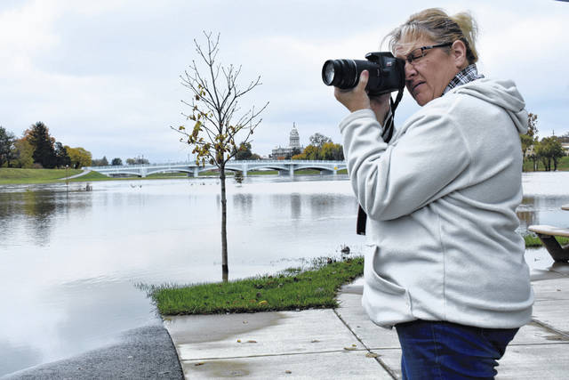 Cody Willoughby | Troy Daily News Lydonna Chaney of Troy snaps photos of the high water on Friday at Treasure Island Municipal Park in Troy.