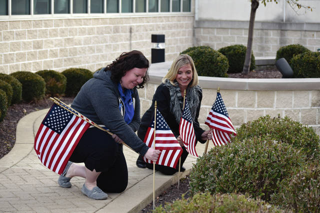 Provided photo UVMC Future Leaders co-chairs Wendy Fullerton, left, and Jenny Jones place memorial flags on the hospital campus in honor of veterans.