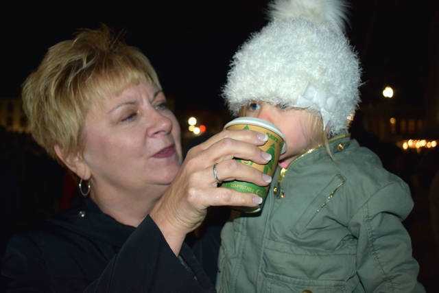 Cody Willoughby | Troy Daily News Brenda Minnich of Troy offers a sip of cider to Louise Starry, 17 months, during the Grand Illumination on Friday, Nov. 23 in Troy.