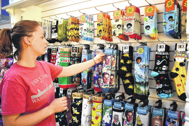 Cody Willoughby | Troy Daily News Employee Sarah Wick, of Troy rearranges selections on the sock wall at Grandpa Joe's Candy Shop, set to open on Thursday in the Public Square in Troy.