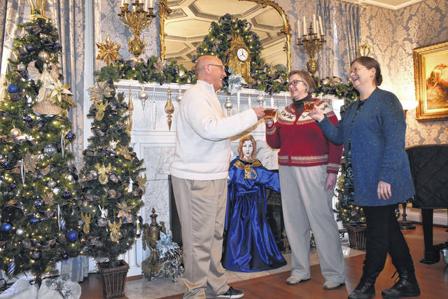 Cody Willoughby | Troy Daily News Hayner Executive Director David Wion shares a toast with staff members Leona Sargent and Terrilynn Meece in the festively decorated East Room, ahead of the center's annual holiday open house event on Saturday, Dec. 1, and Sunday, Dec. 2.