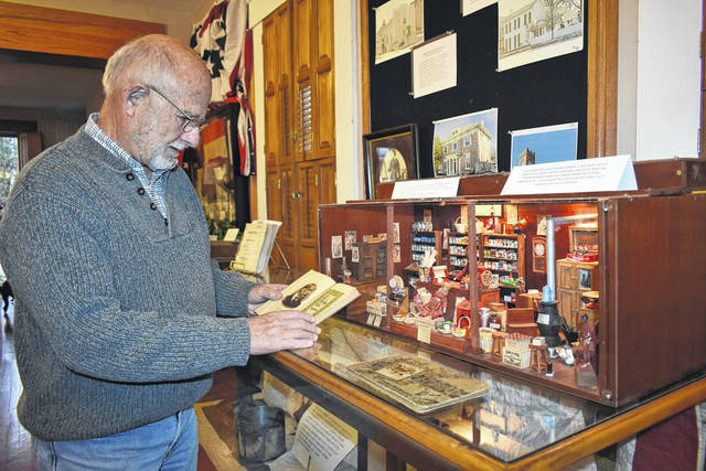Cody Willoughby | Troy Daily News Director Doug Tremblay sets out antique books and postcards near the modular general store designed by the late John Lafferty at the Museum of Troy History, ahead of the facility's annual holiday open house on Saturday, Dec. 1 and Sunday, Dec. 2.
