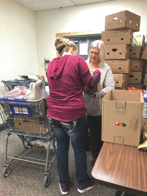 Provided Photo First Place Food Pantry Executive Director Donna Wilkerson helps a patron load up her groceries for her family. The organization will host an open house on Sunday from 12:30-3:30 p.m. to educate the public about its mission and its current funding needs for operation costs.
