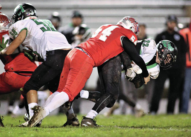Lee Woolery | Troy Daily News Troy's Austan Good (54) tackles a Harrison player in last week's playoff game.