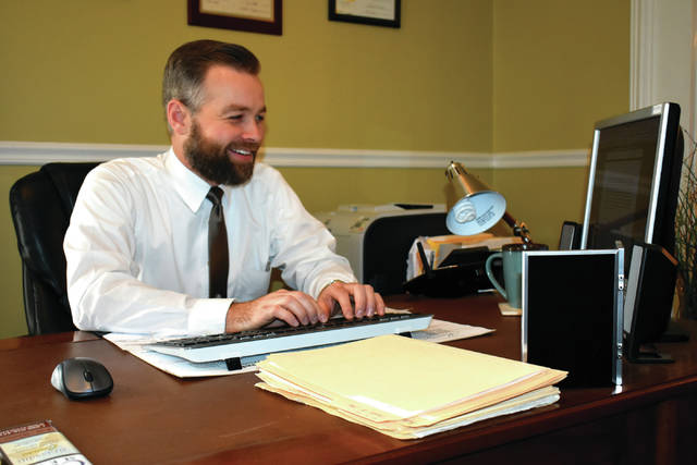 Cody Willoughby | AIM Media Midwest Funeral home director Alex Moore works on his latest installment of &#8220;Calling Around Covington&#8221; &#8212; which appears biweekly in the <em>Daily Call</em> &#8212; in his office at Moore Funeral Home in Covington.