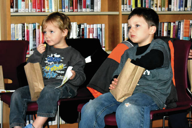 "Cody Willoughby | AIM Media Midwest Jonah and Isaiah McClain, 3 and 5, of Tipp City munch popcorn during a screening of ""A Charlie Brown Thanksgiving"" on Friday at Tipp City Library."