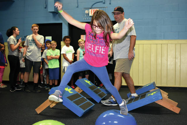 "Cody Willoughby | AIM Media Midwest Alivia Wagner, 8, of Troy leaps across the first obstacles during the ""Troy Rec Ninja Obstacle Challenge"" on Saturday."