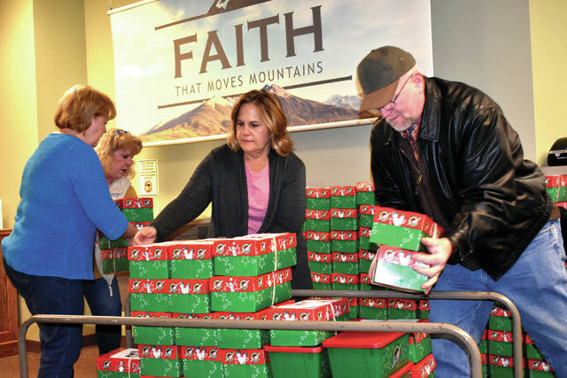 From left, volunteers Dolores Bowers, Robin Oda, Kathy Campbell, and John Bowers unload shoeboxes donated to Operation Christmas Child on Tuesday at Grace Baptist Church in Troy.