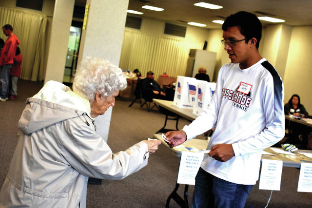 Cody Willoughby | AIM Media Midwest Betty Affolter of Troy collects a sticker from volunteer Michael Vestey, who is a senior at Tippecanoe High School, at the Hobart Corporation polling location on Tuesday.