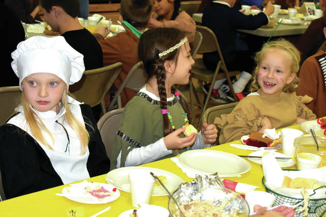 Cody Willoughby | AIM Media Midwest From left, Troy Christian second graders Megan Schramm, Sylvia Rupnik, and Ellie Bigelow enjoy a school-wide Thanksgiving feast on Thursday, Nov. 16 at Troy Christian Elementary School. This marked the 38th year that Troy Christian has held the feast, bringing together 480 students, ages preschool to 6th grade, and 30 returning seniors. Each class helped prepare a different food used in the feast, which utilized over 270 lbs. of turkey, 94 boxes of jello, 41 pumpkin pies, 45 lbs. of noodles, and 174 cans of corn to feed the student body. All food was donated by Troy Christian School board members.