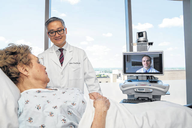 Provided photo Esteban Cheng-Ching, MD, left, with patient, and Bryan Ludwig, MD (on the monitor), are both fellowship-trained neurointerventionalist surgeons with the Premier Health Clinical Neuroscience Institute.