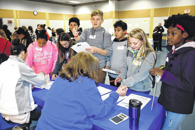 "Cody Willoughby | Troy Daily News Van Cleve sixth-graders debate cell phone, television, and Internet plans at the Communications Station during a financial simulation process, as part of ""Kids at College Day"" on Friday at Edison State Community College in Piqua."