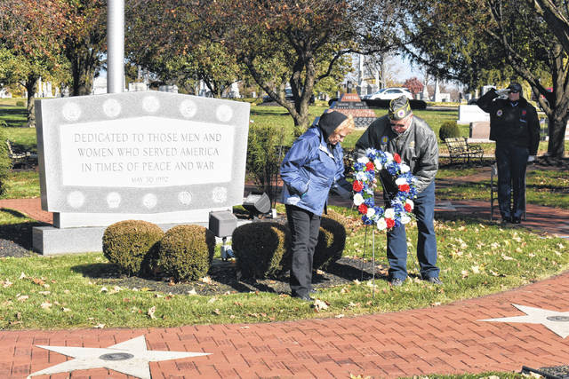 Cody Willoughby   Troy Daily News Mike and Barbara Wilfong, representing AmVets Post 88, place the commemorative wreath at the Veterans Memorial during the Veterans Day ceremony on Sunday at Riverside Cemetery in Troy.