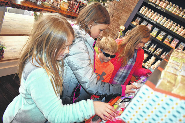 Cody Willoughby | AIM Media Midwest Lauren Spraley, 8, of Columbus, Allie Goff, 10, of Tipp City, and Alex and Jenna Spraley, 6 and 9, of Columbus examine varieties of bath bombs available at Living Simply Soap during Holiday Welcome Weekend on Saturday in Tipp City.