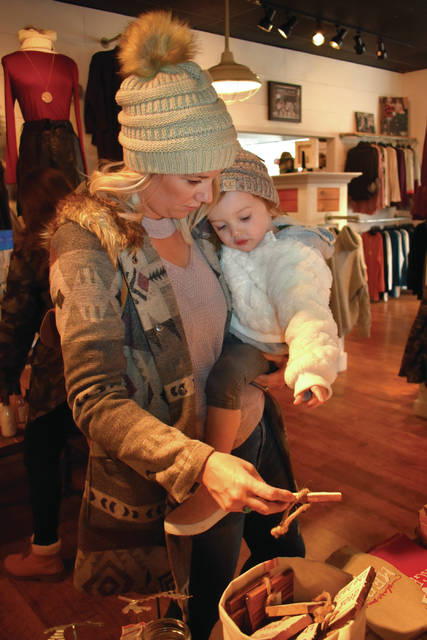 "Cody Willoughby | AIM Media Midwest Lacey West, and daughter Emery, 2, of Washington Courthouse check out merchandise at Ark & Echo during ""Holiday Welcome Weekend"" on Saturday, Nov. 17 in Troy."