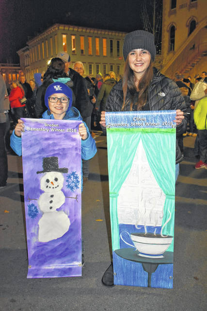 Cody Willoughby | AIM Media Midwest Third grader Braden Wagner and eighth grader Olivia Johnston display their winning submissions from Troy Main Street's holiday/winter banner contest at the Grand Illumination on Friday.