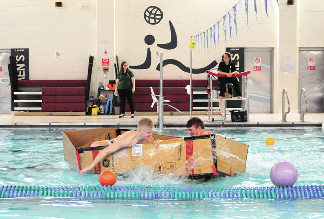 Cecilia Fox | Troy Daily News Tippecanoe High School students Blake Moran and Trevor Traska attempt to steer their boat the length of the pool at the Robinson Branch of the Miami County YMCA