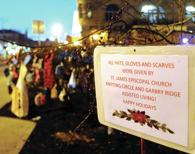 Gloves, mittens, hats, and scarves dangle from bushes in downtown Piqua on Friday, made with love by St. James Episcopal Church Knitting Circle and Garbry Ridge Assisted Living residents. The items are free to anyone in need.