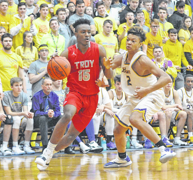 Josh Brown|Miami Valley Sunday News Troy's Caillou Monroe drives around Butler's Matt Beverly Friday at Butler High School.