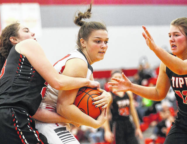 Lee Woolery|Miami Valley Sunday News Troy's Payton Riley battles for a rebound with Tippecanoe's Rachel Wildermuth (23) and Brooke Aselage (12) Saturday at the Trojan Activities Center.