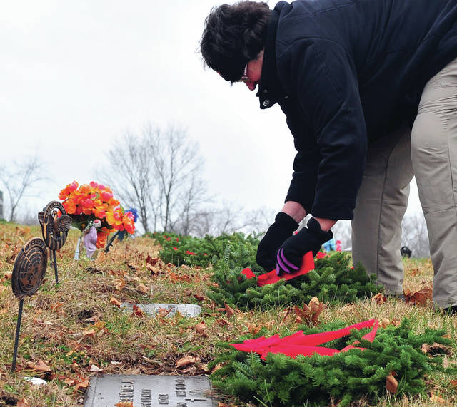 Mike Ullery | Daily Call Cindy Zimmerman of Pleasant Hill places a wreath on the grave of a veteran at Forest Hill Cemetery in Piqua on Saturday as part of the Wreaths Across America Program. More than 800 wreaths were placed by several dozen volunteers. Forest Hill Cemetery is one of more than 1,400 cemeteries, including Arlington National Cemetery, that takes part in this event to honor our nation's veterans.
