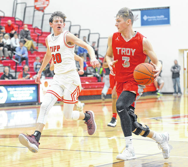 Josh Brown|Miami Valley Today Troy's Austin Stanaford drives on a fast break as Tippecanoe's Ben Knostman tries to catch up Tuesday night at Tippecanoe High School.