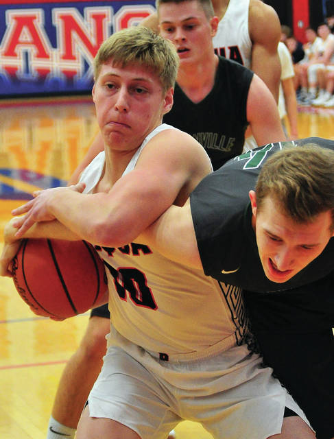 Piqua's Makeegan Kuhn and Greenville's Jordan Dill battle for the ball Tuesday night at Garbry Gymnasium.