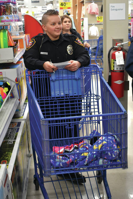 Cody Willoughby | Troy Daily News Piqua police officer Mallory Lash assists shoppers during the Christmas Outreach Program and Services (C.O.P.S.) event on Friday at Meijer in Troy.