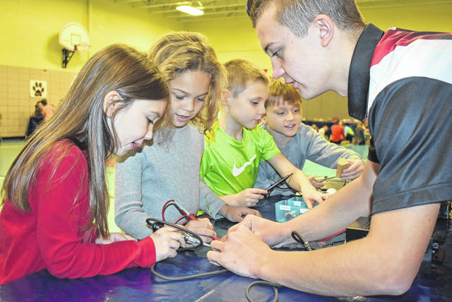 Cody Willoughby | Troy Daily News From left, first graders Audrey Thompson, Joe'de MacGowen, Crosby Murray, and Thane Snyder learn about conductors with student volunteer Preston Gambrell during 'COSI on Wheels' on Tuesday at Cookson Elementary in Troy.