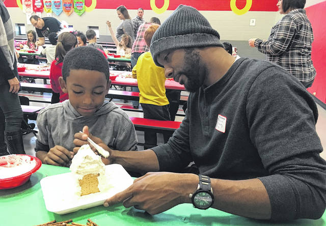 Cody Willoughby | Troy Daily News Third grader D'Andre Gardner receives icing assistance from parent Shorrod Brown during a third-grade gingerbread project on Tuesday at Concord Elementary.