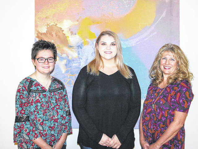 """Provided photo """"Words from Within"""" student editors, left to right, Gabriella Clingman, Mindy Bach, and Kim Kiehl stand in front of artwork created by the late Anne Vacarro."""