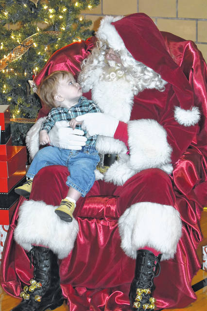 "Cody Willoughby | Troy Daily News Zachary Moore, 9 months, of Piqua meets Santa Claus for the first time during ""Breakfast with Santa"" on Saturday at Lincoln Community Center in Troy."
