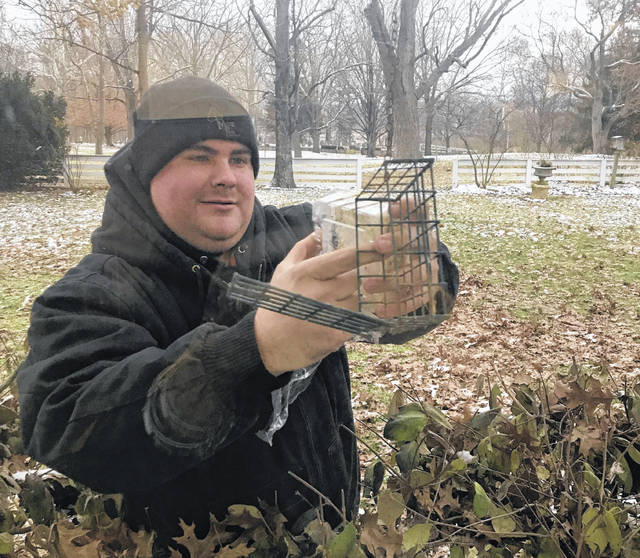 Melody Vallieu | Miami Valley Today Newly appointed Miami County Park Ranger Nathan Metz hangs a suet cake in a feeder at Lost Creek Reserve's Historic Knoop Homestead.