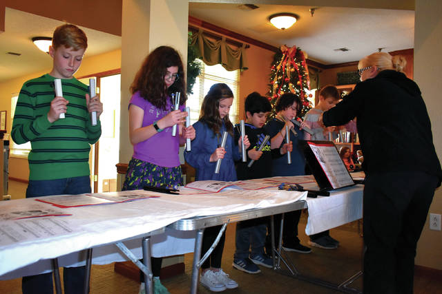Cody Willoughby | Troy Daily News Upper elementary students (grades 4-6) from the Miami Montessori School in Troy play Christmas carols on chimes during a visit to Brookdale Senior Living on Monday, Dec. 17.