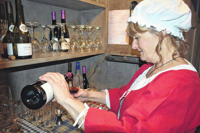 Cody Willoughby | Miami Valley Sunday News Volunteer Brenda Copeland prepares libations for dinner guests during the Overfield Tavern Museum's historic holiday dinner on Saturday in Troy.