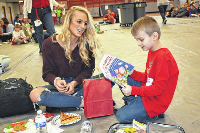 "Cody Willoughby | Troy Daily News THS junior Lily Magoteaux presents a Christmas gift to Concord first grader Addison Shaver during the annual ""Reading Buddies"" holiday party on Friday at Troy High School."