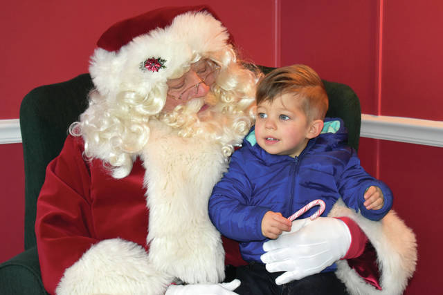 Cody Willoughby | Troy Daily News Paxton Reed, 2, of New Carlisle, visits Santa Claus at Santa's House on Prouty Plaza in Troy on Saturday.