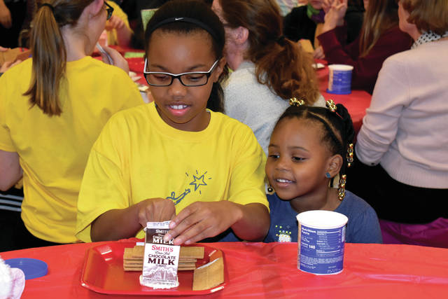 Cody Willoughby | Troy Daily News Concord fifth grader Davonna Harris receives assistance from her 3-year-old sister Dionne during a family gingerbread house event on Wednesday at Troy Junior High, presented by The Future Begins Today.