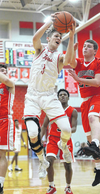 Lee Woolery|Miami Valley Today Troy's Austin Stanaford grabs a rebound in front of a Bellefontaine player Wednesday night at the Trojan Activities Center.