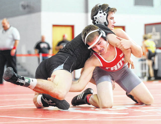 Lee Woolery|Miami Valley Sunday News Covington's Austin Flick battles with Troy's Gabe Cusick during the Troy Invitational Saturday at the Trojan Activities Center.