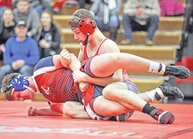 Lee Woolery|Miami Valley Today Troy senior David McGraw works to turn Piqua's Isaac Bushnell during a Senior Night match Wednesday night at Troy High School.