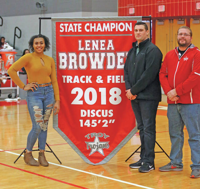 Lee Woolery|Miami Valley Sunday News (From left) Troy's Lenea Browder, throwing coach Aaron Gibbons and girls track and field coach Kurt Snyder stand as Browder receives her state championship banner during halftime of Friday's Troy-Trotwood boys basketball game at the Trojan Activities Center.