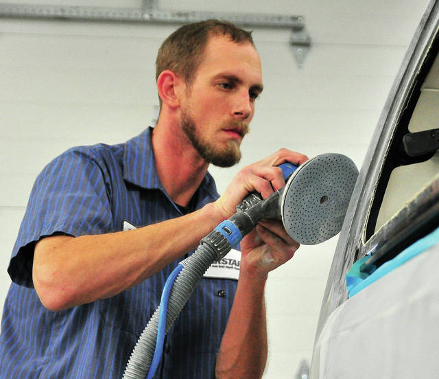 Mike Ullery | Daily Call Piqua CARSTAR Paint Technician Devan Selanders works on a car in the shop earlier this week. Selanders has been with the company since 2011.