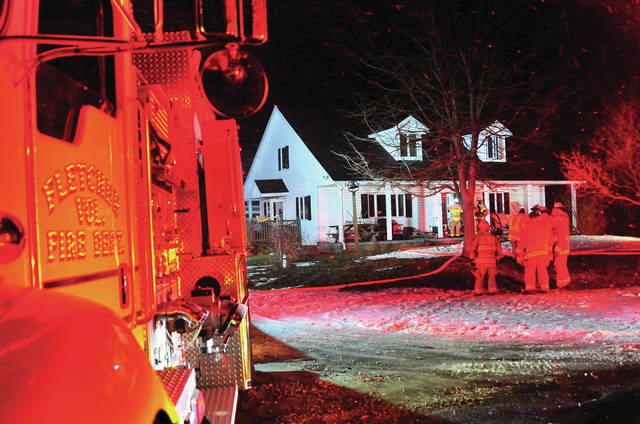 Mike Ullery | Daily Call Firefighters from several area departments work at the scene of a chimney fire on Miami-Shelby Road on Monday evening.