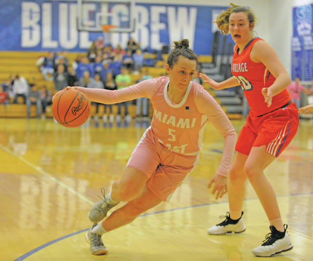 Josh Brown|Miami Valley Today Miami East's Morgan Haney drives past Tri-Village's Meghan Downing Tuesday at Miami East High School.